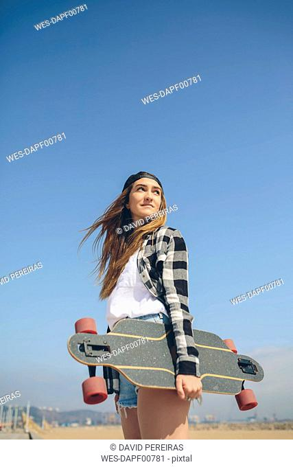Portrait of young woman with longboard