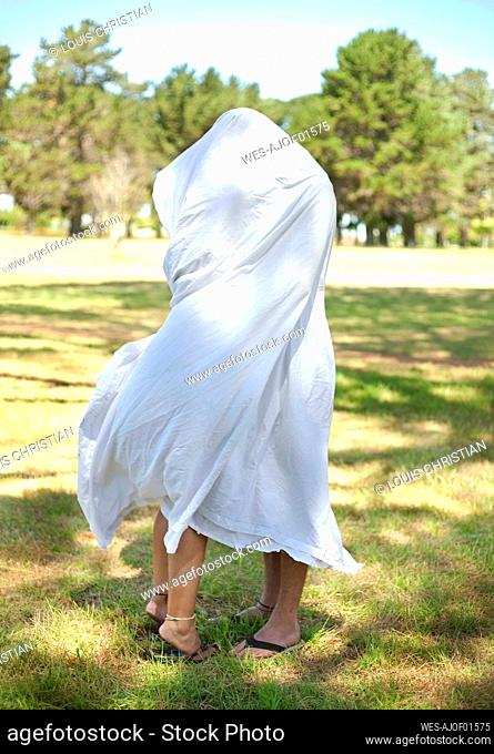 Young couple doing romance under white sheet in public park