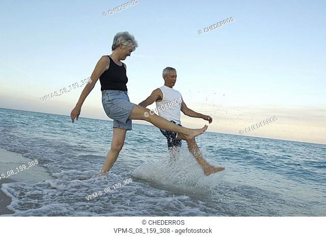 Senior couple splashing water on the beach