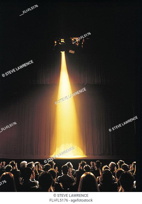 Yellow Spotlight Shining on Empty Theatre Stage, Audience Clapping
