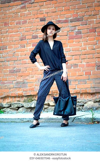 The girl in a black blouse and black hat standing near a brick wall and arch holding a black bag daylight outdoors. Model wearing stylish clothes & accessories