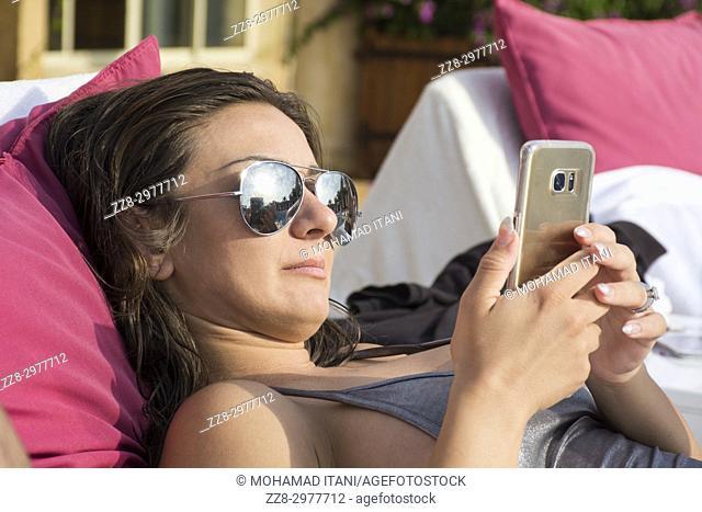 Woman in bikini wearing sunglasses using smart phone while sunbathing