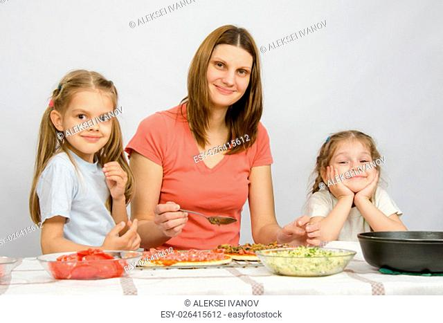 Mum with two little girls sitting at the kitchen table preparing a pizza
