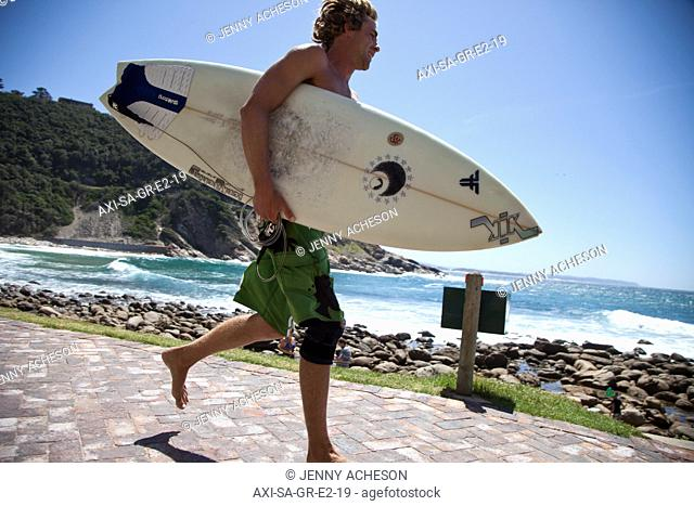 Guy running with surfboard, Victoria Bay, Garden Route, South Africa