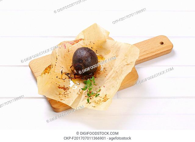 baked whole beet with olive oil and thyme on wooden cutting board