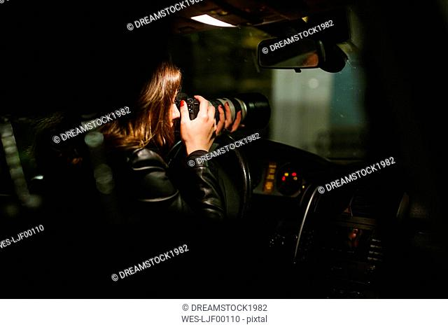 Young woman taking pictures with a camera out of a car at night