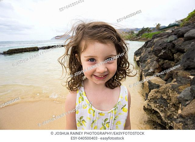 Portrait of a young girl standing in the water at the beach while on vacation to Oahu Hawaii