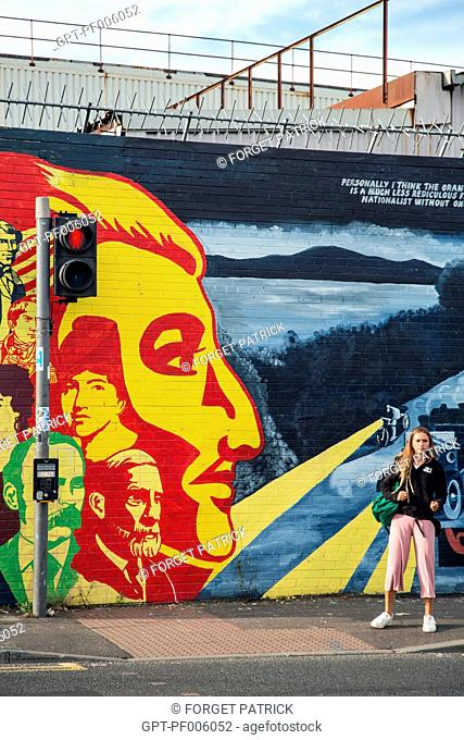 YOUNG WOMAN IN FRONT OF THE MURALS ON THE INTERNATIONAL WALL, DIVIS STREET, BELFAST, ULSTER, NORTHERN IRELAND