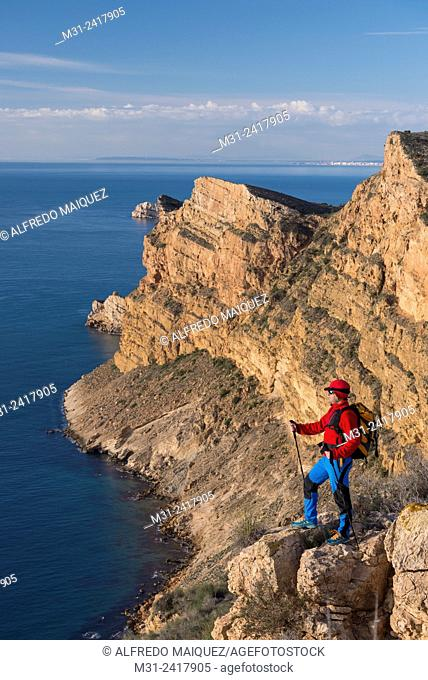 A men looks out over the Mediterranean sea from Sierra Helada natural park cliff, Benidorm, Alicante province, Spain