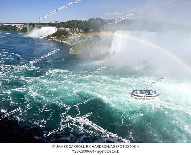 Sightseeing boat at Niagara Falls on Canadian side with rainbow