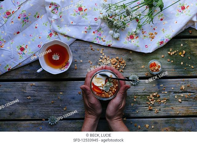 A jar with yoghurt, granola and fresh fruit with two hands on a wooden table with a cup of tea and flowers