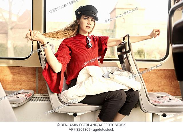 young woman playing with hair style while sitting in public transport, in city Cottbus, Brandenburg, Germany