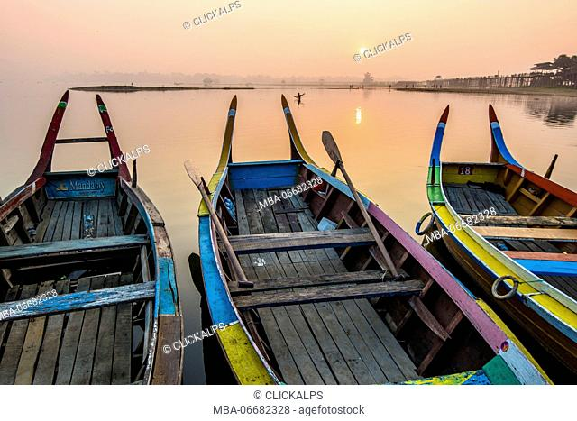 Amarapura, Mandalay region, Myanmar. Colorful boats moored on the banks of the Taungthaman lake at sunrise, with the U Bein bridge in the background