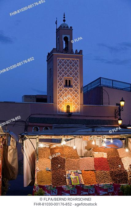 Mosque minaret and market stand in city at dusk, Djemaa el Fna, Marrakesh, Morocco, april