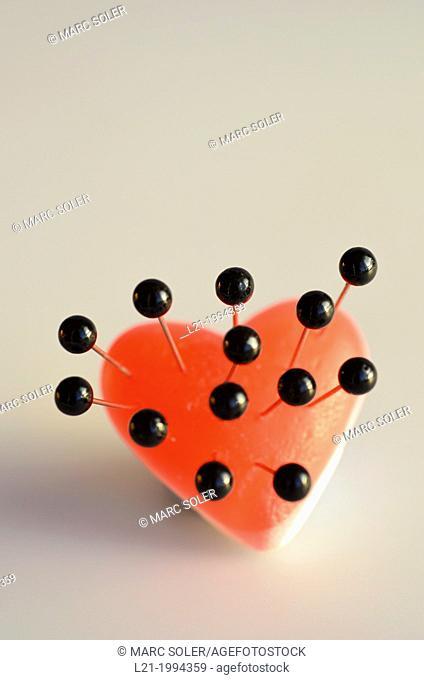 Black thumbtacks on a red heart. Evil heart, heartache, heart sick, broken heart