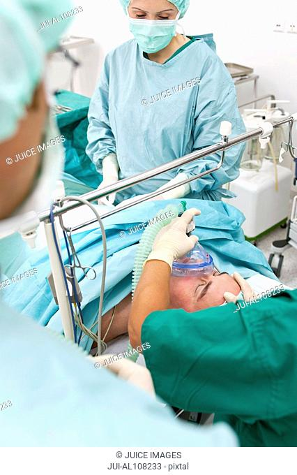 Doctor and nurses in operating room putting patient under anesthesia during surgery
