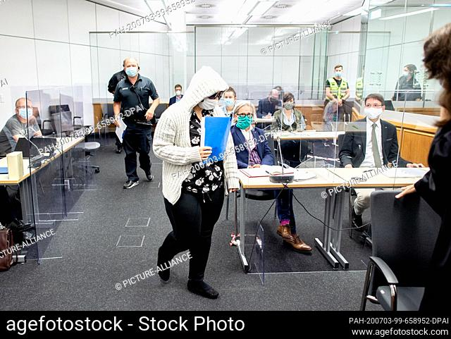 03 July 2020, Lower Saxony, Celle: The accused (M) enters a room of the Higher Regional Court with sunglasses and mouth protection before the beginning of the...