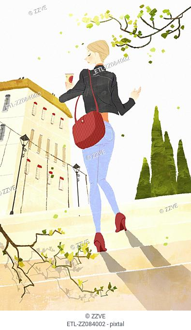 Young woman stepping toward the building holding the cold drink