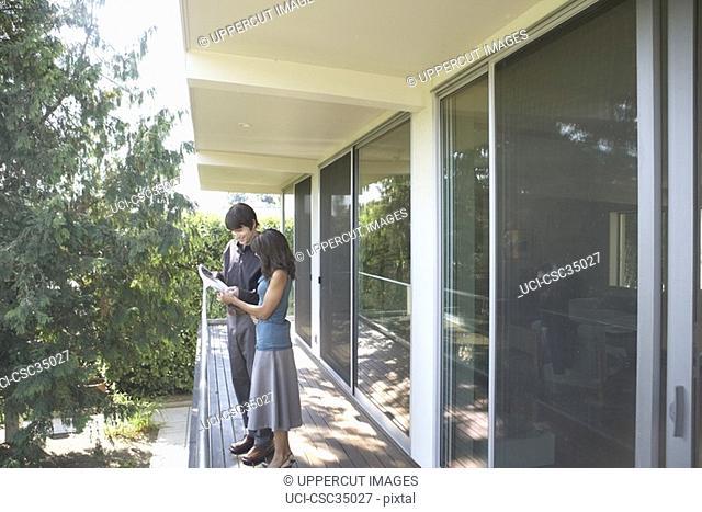 Couple reading newspaper on balcony