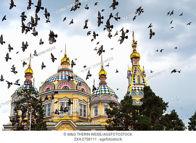 Pigeons flying over the Ascension Cathedral or Zenkov Cathedral, Panfilov Park, Almaty, Kazakhstan, Central Asia