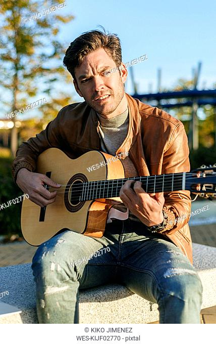 Portrait of man playing guitar outdoors