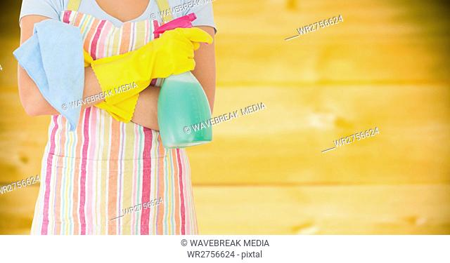 Woman in apron with cleaner against blurry yellow wood panel