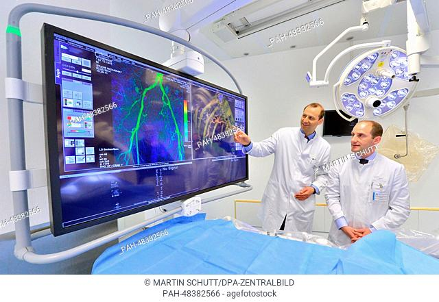 Director of the Radiology Center Ulf Teichgraeber (L) and senior physician Rene Aschenbach look at the new angiography system on a hospital employee at the...