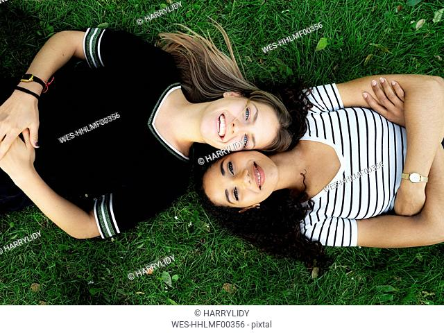 Two girlfriends relaxing in a park, lying on grass