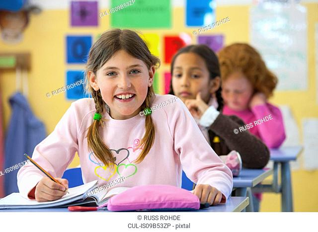 Portrait of primary schoolgirl writing in classroom