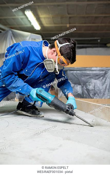 Worker treating the cement floor with a jackhammer