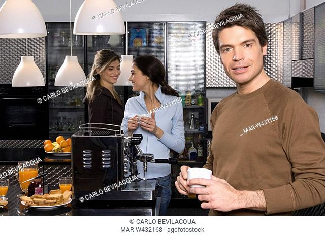 young women and man in kitchen, breakfast
