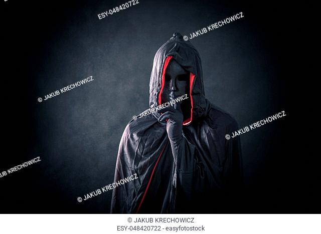 Scary figure with black mask in hooded cloak
