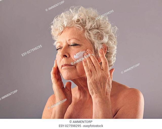 Portrait of senior woman putting on anti-aging cream on her face against grey background. Anti-ageing concept, woman in her 70s applying skin cream on her face