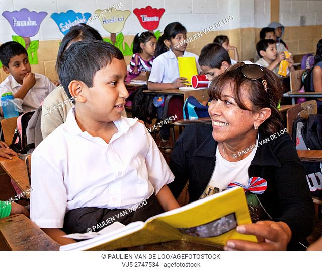 Mixco, Guatemala, Sandra Reemer (dutch famous artist) is reading a book to a boy in school. Sandra sponsored this school together with other investors to give...