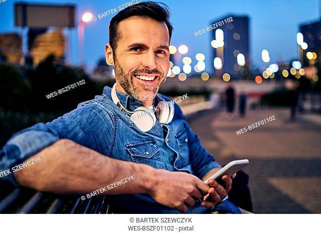Portrait of a smiling man using his smartphone while sitting on a bench in the evening