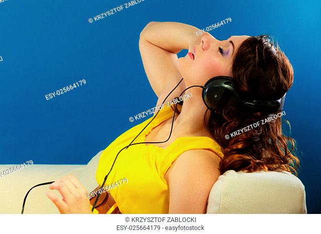 young people relax leisure concept. closeup of a cute teen girl in big headphones listening music mp3 relaxing on blue background