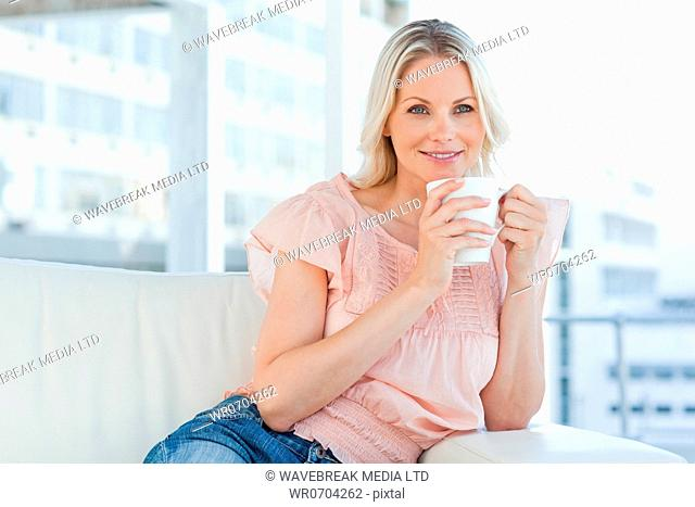 Blonde with a cappuccino in a bright living room
