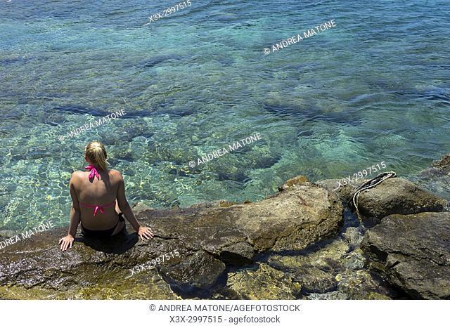 Girl sitting on the beach. Naxos island, Greece