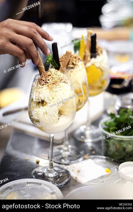 Detalle del personal que hace sundae de helado de gelato italiano en la tienda moderna