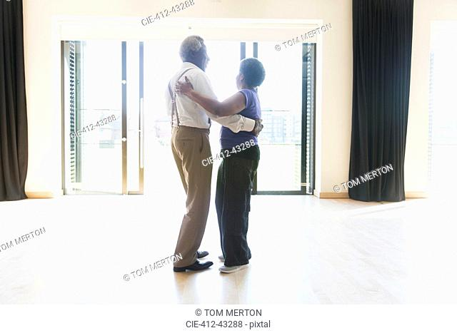 Active senior couple dancing in dance studio