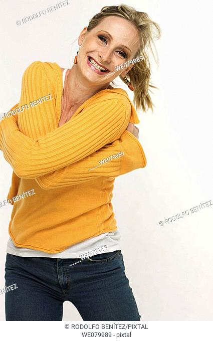 Blond woman hugging herself and smiling in the studio