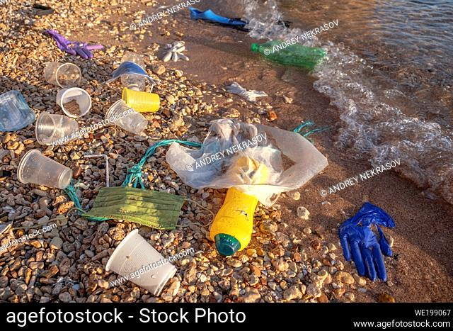 RED SEA, SHARM EL SHEIKH, EGYPT - OCTOBER 18-26, 2020: Plastic debris and face masks on the beach in surf zone. Coronavirus COVID-19 is contributing to...