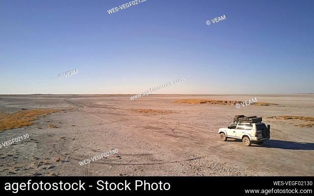 Botswana, Aerial view of 4x4 car crossing Makgadikgadi Pan