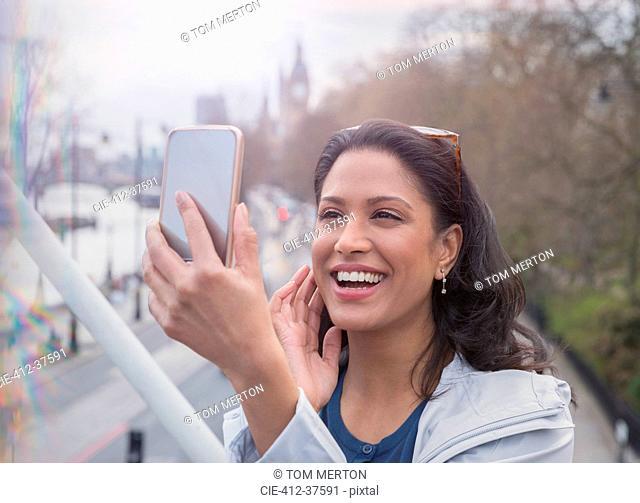 Smiling, confident woman taking selfie with camera phone on urban bridge