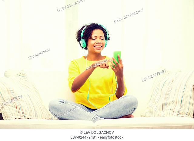 people, technology and leisure concept - happy african american young woman sitting on sofa with smartphone and headphones listening to music at home