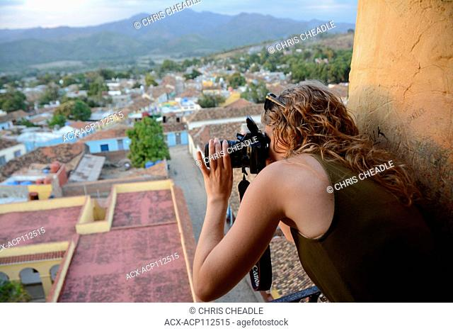 Young woman photographs from the opening of the tower at Iglesia y Convento de San Francisco, Trinidad, Cuba