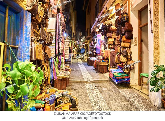 Tourists and souvenir shops selling Moroccan handicrafts at night, Granada, Andalusia, Spain, Europe