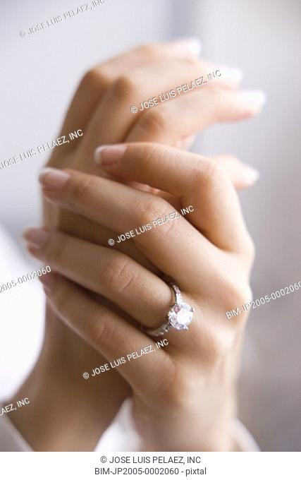 Young woman's manicured nails wearing an engagement ring