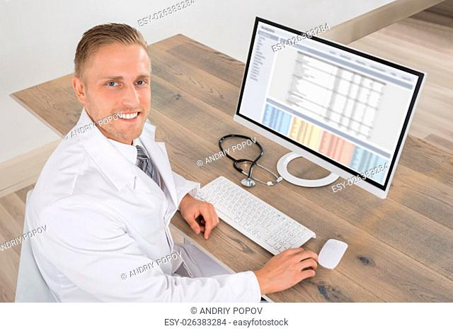 Happy Young Doctor Working On Computer At Desk
