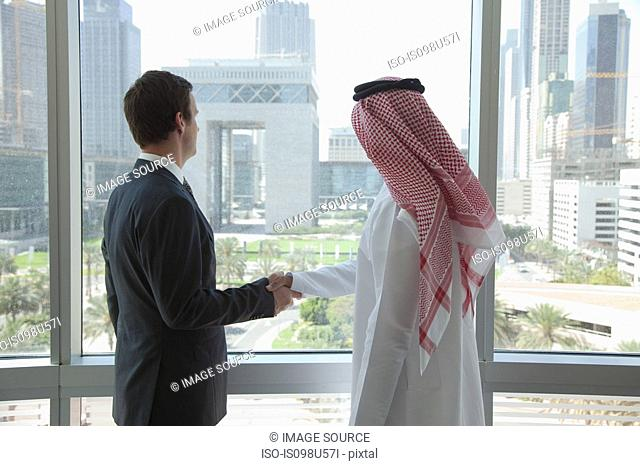 Western and middle eastern businessmen shaking hands by window